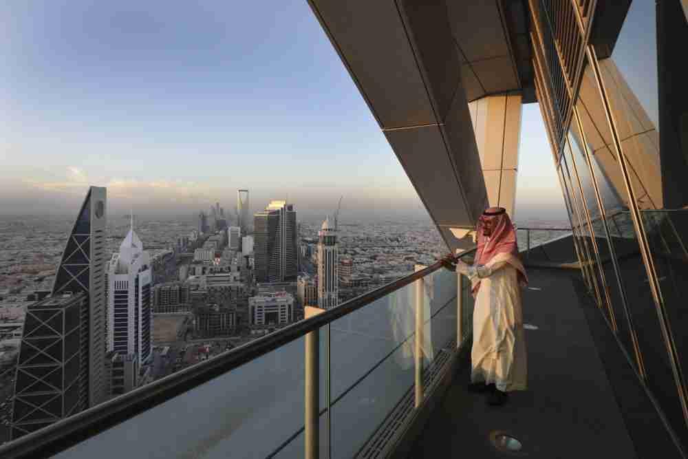 موظف في برج الفيصلية ينظر إلى أفق المدينة في الرياض، المملكة العربية السعودية، يوم الخميس، 1 ديسمبر 2016. الصورة: سيمون داوسون، بلومبيرغ.