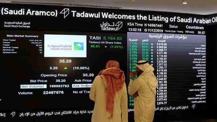 يراقب المستثمرون شاشة تعرض معلومات الأسهم في السوق المالية السعودية (تداول) بعد طرح الاكتتاب العام الأولي لشركة أرامكو السعودية في سوق الأوراق المالية في الرياض، في الرياض، المملكة العربية السعودية، 11 ديسمبر 2019. الصورة: أحمد يسري، رويترز.